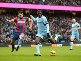 Manchester City's Ivorian midfielder Yaya Toure shoots to score their third goal as Crystal Palace's Australian midfielder Mile Jedinak closes in during the English Premier League football match between Manchester City and Crystal Palace at the Etihad Sta