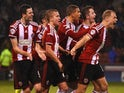 Marc McNulty of Sheffield United (protective mask) celebrates scoring the opening goal with team mates during the Capital One Cup Quarter-Final match against Southampton on December 16, 2014