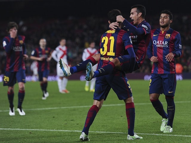 Barcelona's forward Pedro Rodriguez (up) is congratulated by his teammate Barcelona's forward Munir el Haddadi after scoring during the Spanish Copa del Rey match agains Huesca on December 16, 2014