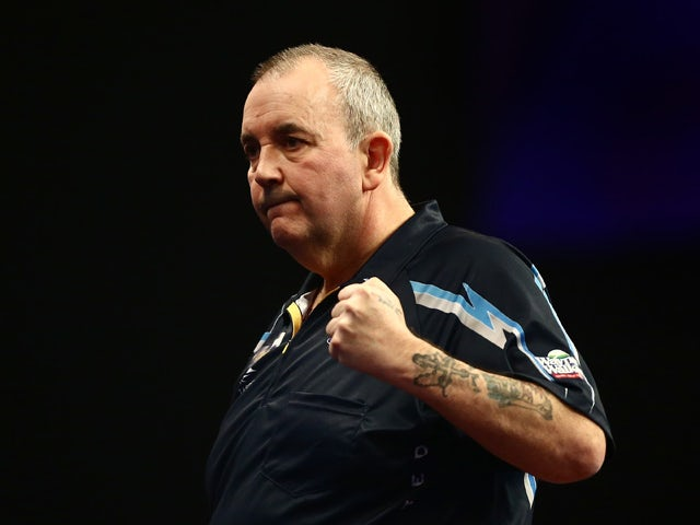 Phil Taylor of England celebrates winning his first round match against Jyhan Artut of Germany on Day Two of the William Hill PDC World Darts Championships at Alexandra Palace on December 19, 2014