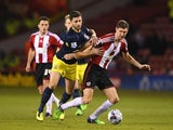 Shane Long of Southampton challenges Chris Basham of Sheffield United during the Capital One Cup Quarter-Final match on December 16, 2014