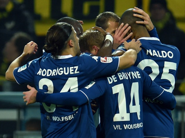 Wolfsburg's players celebrate during the German First division Bundesliga football match Borussia Dortmund v VfL Wolfsburg in Dortmund, Germany, on December 17, 2014