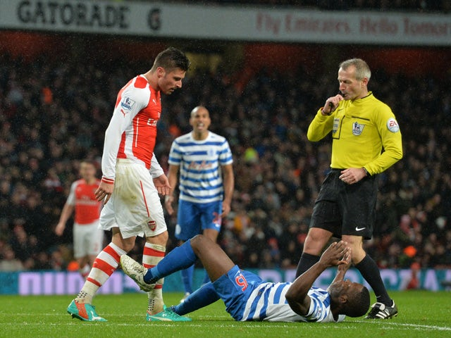 Queens Park Rangers' English defender Nedum Onuoha goes down after a confrontation with Arsenal's French striker Olivier Giroud in front of referee Martin Atkinson (C) after which Giroud is sent off during the English Premier League football match between