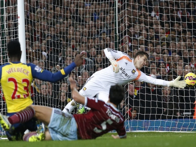 Arsenal's English striker Danny Welbeck (L) sends an attempt wide as West Ham United's Spanish goalkeeper Adrian (R) dives to cover during the English Premier League football match on December 28, 2014