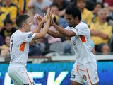Jean Carlos Solorzano of the Roar celebrates a goal with team mate Matthew McKay during the round 13 A-League match against the Central Coast Mariners on December 27, 2014