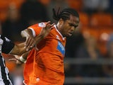 Nathan Delfouneso of Blackpool holds off a challenge from Ikechi Anya of Watford during the Sky Bet Championship match between Blackpool and Watford at Bloomfield Road on September 16, 2014
