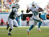 Running back Lamar Miller #26 of the Miami Dolphins tries to elude cornerback Marcus Williams #22 of the New York Jets in the second quarter during a game at Sun Life Stadium on December 28, 2014