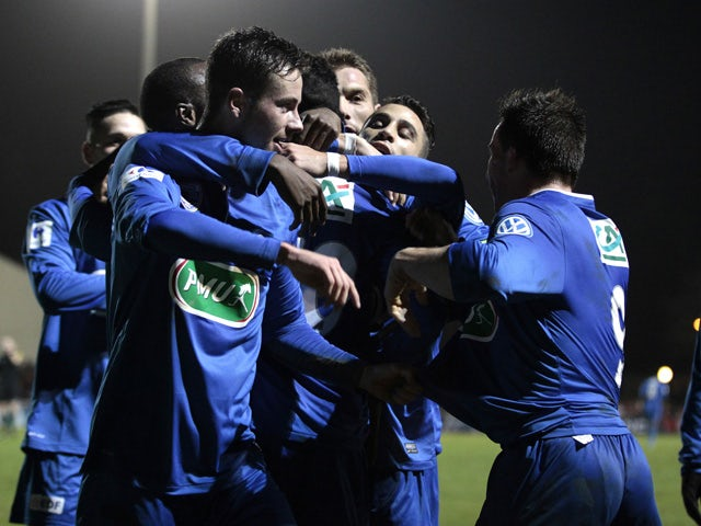 Avranches' forward Vincent Crehin celebrates with teammates after scoring a goal during a French Cup round of 64 football match between Avranches and Lorient on January 3, 2015