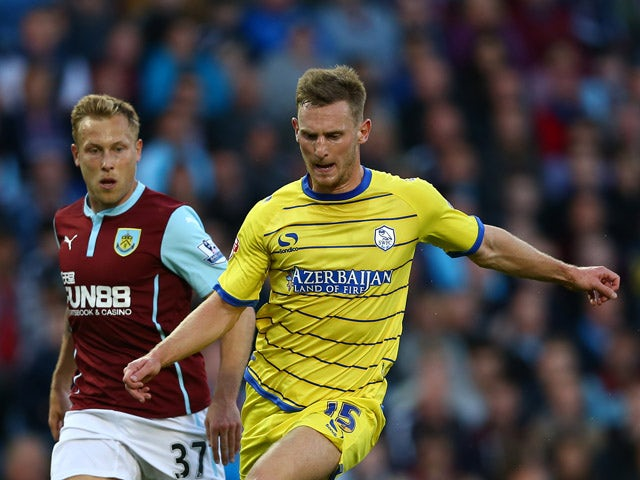 Tom Lees of Sheffield Wednesday in action with Scott Arfield of Burnley during the Capital One Cup Second Round match between Burnley and Sheffield Wednesday at Turf Moor on August 26, 2014