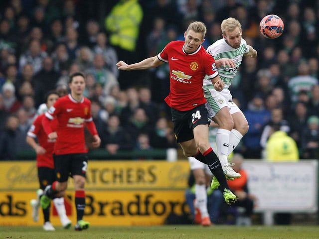 Manchester United's Scottish midfielder Darren Fletcher and Yeovil Town's English midfielder Simon Gillett contest a high ball during the English FA Cup third round football match between Yeovil Town and Manchester United at Huish Park in Yeovil, Somerset