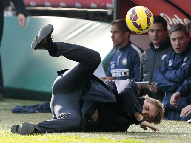 Inter Milan coach Roberto Mancini is struck by a ball during the Italian Serie A football match Inter Milan vs Genoa on January 11, 2015