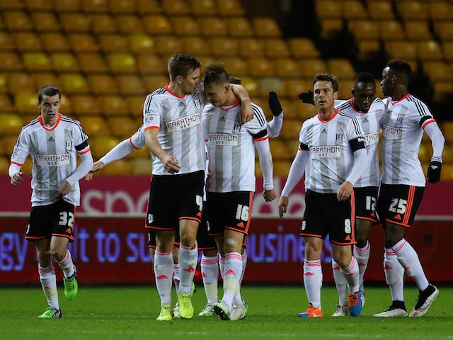 Cauley Woodrow of Fulham celebrates with team-mates after scoring the opening goal during the FA Cup third round replay match against Wolves on January 13, 2015