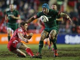 Rhys Priestland of Scarlets passes the ball as Graham Kitchener of Leicester Tigers moves in to tackle during the European Rugby Champions Cup Group 3 match between Leicester Tigers and Scarlets at Welford Road on January 16, 2015