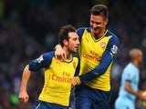 Santi Cazorla of Arsenal (L) celebrates with Olivier Giroud as he scores their first goal from a penalty during the Barclays Premier League match against Man City on January 18, 2015