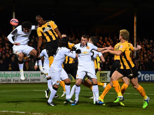Tom Elliott of Cambridge United heads towards goal under pressure from Marouane Fellaini of Manchester United during the FA Cup Fourth Round match between Cambridge United and Manchester United at The R Costings Abbey Stadium on January 23, 2015