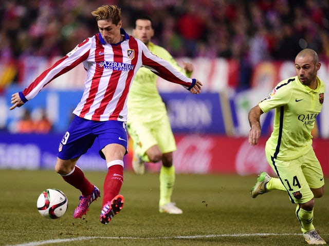 Atletico Madrid's forward Fernando Torres shoots to score past Barcelona's Argentinian midfielder Javier Mascherano during the Spanish Copa del Rey (King's Cup) quarter final second leg football match Club Atletico de Madrid vs FC Barcelona at the Vicente