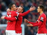 Robin van Persie of Manchester United is congratulated by teammates Wayne Rooney and Adnan Januzaj after scoring his team's first goal during the Barclays Premier League match between Manchester United and Leicester City at Old Trafford on January 31, 201