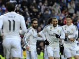 Real Madrid's French forward Karim Benzema celebrates with teammates after scoring during the Spanish league football match Real Madrid CF vs Real Sociedad de Futbol at the Santiago Bernabeu stadium in Madrid on January 31, 2015
