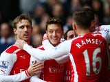 Mesut Ozil of Arsenal celebrates scoring the opening goal with team mates during the Barclays Premier League match between Tottenham Hotspur and Arsenal at White Hart Lane on February 7, 2015