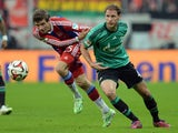 Bayern Munich's striker Thomas Muller and Schalke's defender Benedikt Howedes vie for the ball during the German first division Bundesliga football match FC Bayern Munich vs FC Schalke 04 at the Allianz Arena in Munich, southern Germany, on February 3, 20
