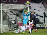 Evian's French forward Mathieu Duhamel vies with Bordeaux's French goalkeeper Cedric Carrasso during the French L1 football match Evian (ETGFC) against Bordeaux (FC) on february 7, 2015