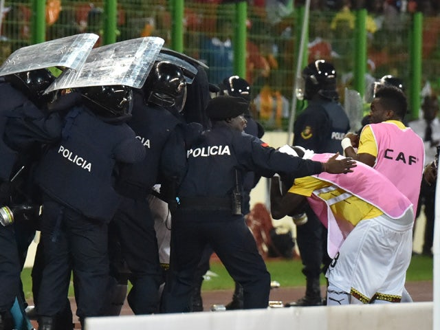 Ghana's national football team players leave the pitch protected by riot police at the half-time of the 2015 African Cup of Nations semi-final football match between Equatorial Guinea and Ghana in Malabo, on February 5, 2015