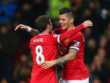 Juan Mata of Manchester United congratulates Marcos Rojo of Manchester United on scoring their second goal during the FA Cup Fourth round replay match between Manchester United and Cambridge United at Old Trafford on February 3, 2015