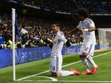 Real Madrid's Colombian midfielder James Rodriguez celebrates past Real Madrid's Brazilian defender Marcelo after scoring during the Spanish league football match Real Madrid CF vs Sevilla FC at the Santiago Bernabeu stadium in Madrid on February 4, 2015