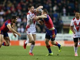 Joe Greenwood of St Helens crashes through the tackle of Ben Pomeroy and Thomas Bosc of Catalans Dragons during the First Utility Super League match between St Helens and Catalans Dragons at Langtree Park on February 6, 2015