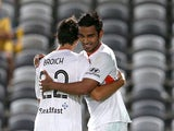 Jean Carlos Solorzano celebrates a goal with Thomas Broich of the Roar during the round 17 A-League match between the Central Coast Mariners and the Brisbane Roar at Central Coast Stadium on February 13, 2015