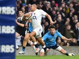 England's centre Jonathan Joseph slips a tackle to run in and score England's second try during the Six Nations international rugby union match between England and Italy at Twickenham Stadium in south west London on February 14, 2015