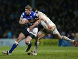 Liam Sutcliffe of Leeds Rhinos is tackled by Hep Cahill of Widnes Vikings during the First Utility Super League match between Leeds Rhinos and Widnes Vikings at Headingley Carnegie Stadium on February 13, 2015