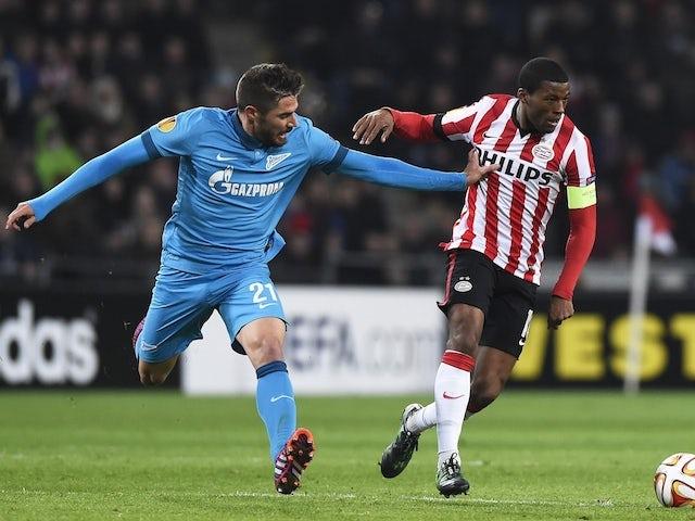 PSV Eindhoven's Georginio Wijnaldum (R) fights for the ball with Zenit Saint Petersburg's Javi Garcia (L) on February 19, 2015