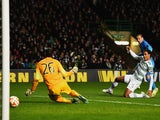 Rodrigo Palacio of Inter Milan shoots past goalkeeper Craig Gordon and Virgil van Dijk of Celtic to score their second goal during the UEFA Europa League match on February 19, 2015