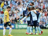 Rhyan Grant of Sydney FC celebrates with team mates after scoring a goal as Alex Brosque of Sydney FC jumps over the top during the round 18 A-League match between Sydney FC and the Central Coast Mariners at Allianz Stadium on February 21, 2015
