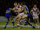Louie McCarthy-Scarsbrook of St Helens is tackled by Daryl Clark and Chris Hill of Warrington Wolves during the World Club Series match between Warrington Wolves and St George Illawarra Dragons at The Halliwell Jones Stadium on February 20, 2015