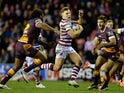 George Williams of Wigan Warriors gets past Sam Thaiday of Brisbane Broncos during the World Club Series match between Wigan Warriors and Brisbane Broncos at DW Stadium on February 21, 2015