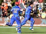 Afghanistan batsman Shapoor Zadran celebrates with teammate Hamid Hassan after hitting the winning runs to defeat Scotland in their 2015 Cricket World Cup Group A match in Dunedin on February 26, 2015