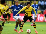 Schalke's defender Dennis Aogo and Dortmund's Japanese midfielder Shinji Kagawa (R) vie for the ball during the German first division Bundesliga football match on February 28, 2015