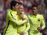 Barcelona's Croatian midfielder Ivan Rakitic (C) celebrates a goal with teammates Barcelona's Uruguayan forward Luis Suarez against Granada on February 28, 2015