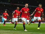 Wayne Rooney of Manchester United celebrates scoring the opening goal with Marcos Rojo and Ashley Young of Manchester United during the Barclays Premier League match between Manchester United and Sunderland at Old Trafford on February 28, 2015