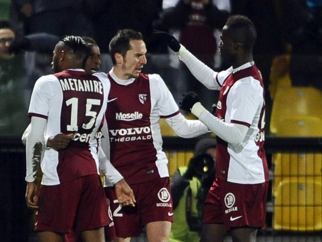Metz' players celebrate after their French midfielder Bouna Sarr scored a goal during the French L1 football match between Metz (FCM) and Evian (ETGFC) on February 28, 2015