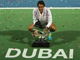 Roger Federer of Switzerland poses with the ATP Dubai Duty Free Tennis Championships trophy after defeating World number one Novak Djokovic of Serbia during their final on February 28, 2015