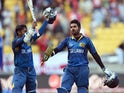Sri Lanka batsmen Kumar Sangakkara and Lahiru Thirimanne wave to fans after hitting the winning runs against England during their 2015 Cricket World Cup Group A match in Wellington on March 1, 2015