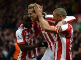 Peter Crouch of Stoke City celebrates scoring the first goal with team-mates Victor Moses and Jonathan Walters during the Barclays Premier League match between Stoke City and Hull City at Britannia Stadium on February 28, 2015