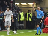 Atletico Madrid's Portuguese midfielder Tiago (L) is given the red card from Czech referee Pavel Kralovec during the UEFA Champions League first-leg, round of 16 football match against Bayer 04 Leverkusen on February 25, 2015