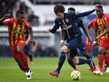 Paris Saint-Germain's French midfielder Adrien Rabiot (C) advances with the ball past Lens' French defender Loick Landre (L) during the French L1 football match  on March 7, 2015
