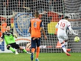 Lyon's French forward Alexandre Lacazette (R) scores from a penalty during the French L1 football match between Montpellier and Lyon, on March 8, 2015