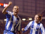 Porto's Costinha (L) celebrates as teammate Maniche joins hime after scoring against Manchester United in the final minute of a Champions League tie on March 9, 2004