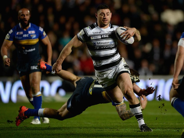 Mark Minichiello of Hull FC jumps from a tackle from Adam Cuthbertson of Leeds Rhinos during the First Utility Super League match between Hull FC and Leeds Rhinos at KC Stadium on March 5, 2015